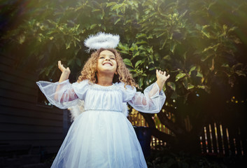 Mixed race girl wearing angel costume in backyard