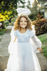 Mixed race girl wearing angel costume on sidewalk