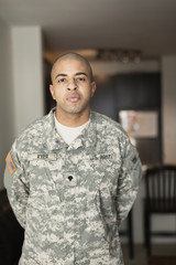 Mixed race soldier standing in living room