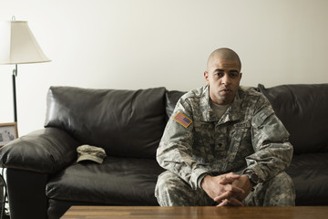 Mixed race soldier sitting on living room sofa