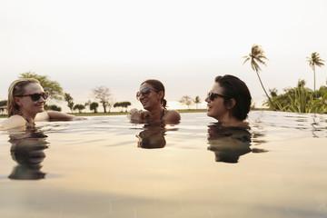 Smiling women relaxing in infinity pool