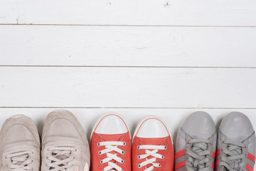 A picture of different shoes, Shot of several types of shoes, Several designs of  women shoes. Leather Shoe, Sport Shoe. Pile of various female shoes on wooden background