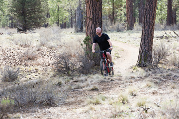 Bald man riding a mountain bike on a dirt trail in the forest