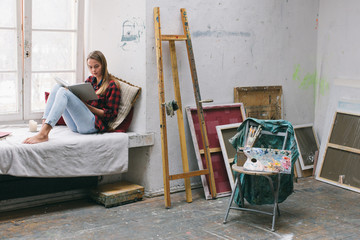 Painter woman resting in the workshop