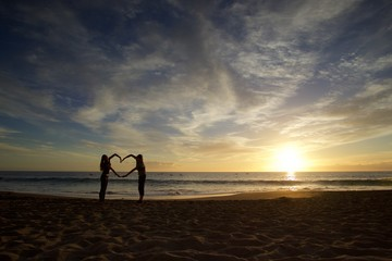 Couple, woman and man make heart by hands on the beach at sunset with sea on the background. Lovers on valentines day on vacation. Spain.