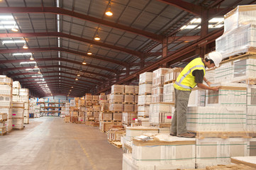 Hispanic worker checking inventory in warehouse