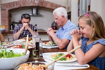 Multi-generation family praying before having meal