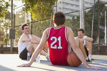 Caucasian men sitting on urban basketball court