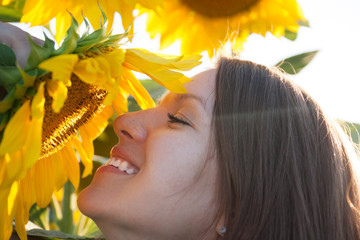 Woman is smelling the sunflower
