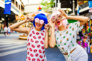 Two bright funny cool fashionable girl in blue and pink wig posing against the backdrop of carousels in amusement park. In the hands holding the sweet donuts.