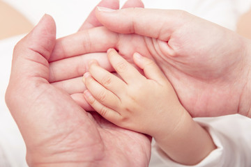 Hand the sleeping baby in the hand of mother close-up (Soft focu