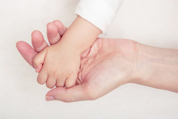 Baby hand gently holding adult's finger (Soft focus and blurry)