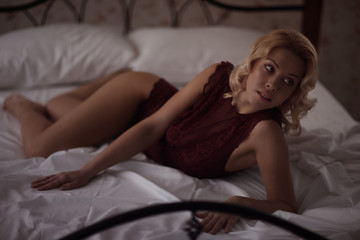 Beautiful smiling blond woman with long slim legs posing bedroom