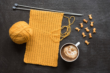 Yellow knitting, cup of coffee and fish crackers
