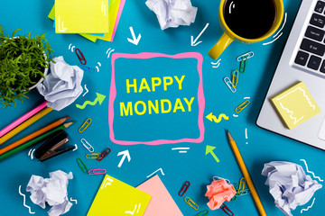 Happy Monday. Office table desk with supplies, white blank note pad, cup, pen, pc, crumpled paper, flower on blue background. Top view