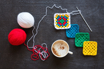 Red and white yarn, crocheted motives and coffee