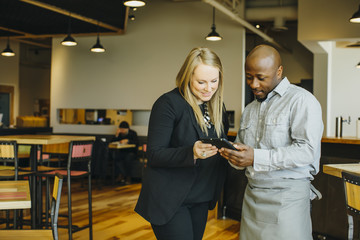 Waiter and businesswoman using cell phones in cafe