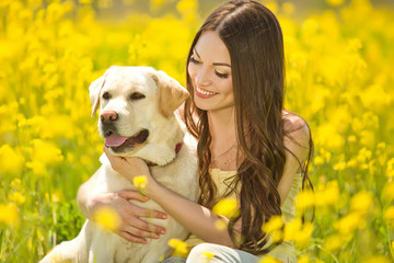 woman with labrador in a flowers field