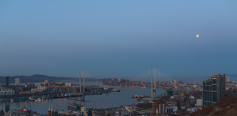 Vladivostok cityscape. Early morning. With moon in the sky. High-res photo.