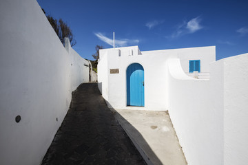 White walls and alleyway under blue sky