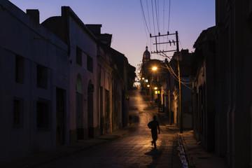 Pedestrian walking on Santiago de Cuba street at night, Santiago, Cuba