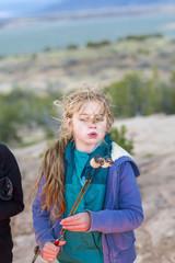 Caucasian girl toasting marshmallows at campfire