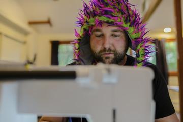 Caucasian man wearing fuzzy hat using sewing machine