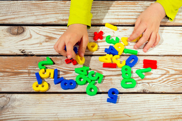 Children digits on the table. Child takes numbers