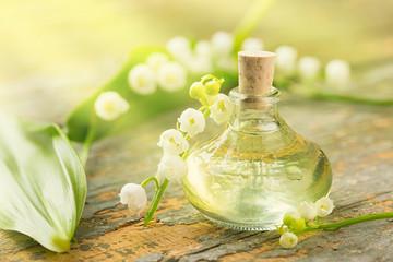 Maiglöckchen - Ätherisches Öl - Flasche und Blüten auf Holz Fototapete