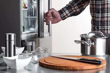 Kochzubehör vor einem offenen Kühlschrank