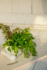 Mix Fresh Green Herbs.  Thyme, Rosemary, Dill and Parsley in the mortar on white background.