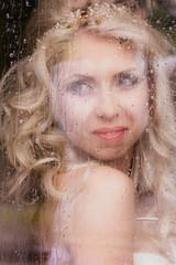Beautiful romantic blonde bride posing near rainy window face cl