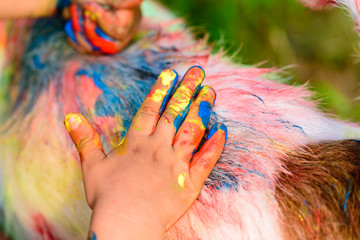 Child painting on a dog back colorful art scene