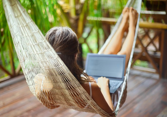 Young woman lying in a hammock with laptop in a tropical resort.