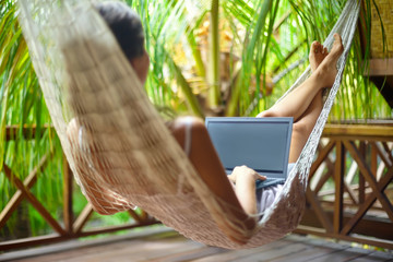 beautiful woman lying in a hammock with laptop in a tropical res