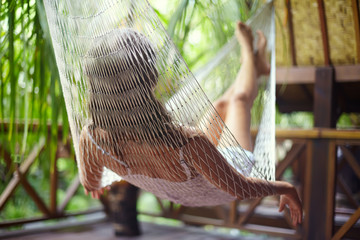Young woman relaxing in hammock in a tropical resort.back view