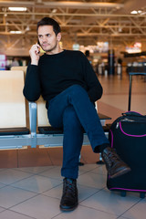 Portrait of handsome smiling man in casual wear, with his mobile phone while sitting in the hall of the airport terminal, while waiting for his flight.