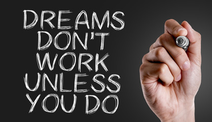 Hand writing the text: Dreams Don't Work Unless You Do