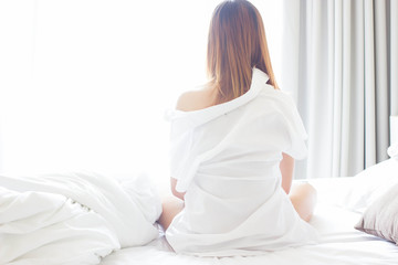 The women on the bed in the morning.