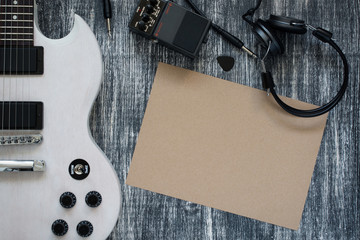 Electric guitar on wooden grey background, sheet of paper, earphone, Overdrive Effects Pedals