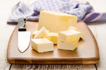 butter cubes and kitchen knife on a wooden board