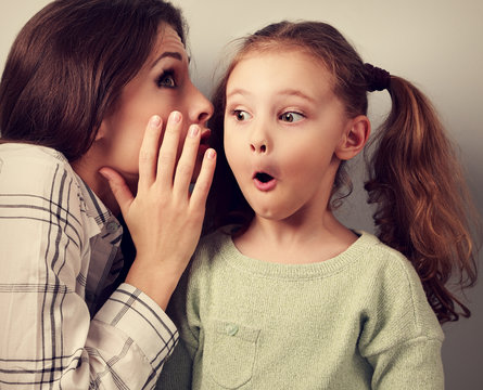 Shocked mother whispering the secret information to her surprisi