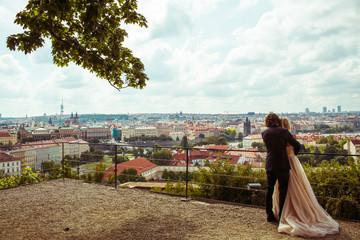 Sensual newlywed hugging on honeymoon, cityscape of Prague, groo