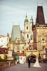 Wall Murals Prague Happy romantic brid & groom holding hands on bridge in Prague