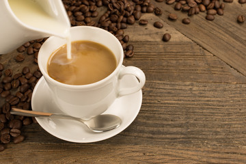 Pouring milk in a cup of coffee and beans on wooden background