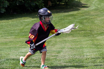 Child wearing black jersey and protective equipment playing lacr