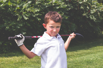 Little boy golfer with driver club over shoulders posing for cam