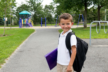 Happy little boy with school backpack and book in the play yard