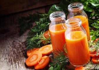 Freshly squeezed juice of carrots in glass bottles, vintage wood