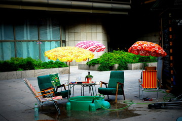 Street scene with umbrellas, armchairs and table